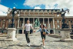 Vue intégrale des couples assez jeunes dans l'amour tenant des mains tout en marchant le long du countryard chez Buda Castle Photographie stock libre de droits