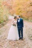 Vue intégrale des nouveaux mariés de baiser sur la route près du bois d'automne Photographie stock