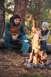vue intégrale du père et du fils faisant cuire des guimauves au feu de camp photographie stock libre de droits