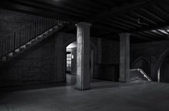 Vue intérieure d'un vieux bâtiment avec des colonnes et d'escalier avec quelques faisceaux lumineux dans l'entourage foncé illustration libre de droits