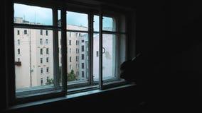 Vue intérieure de fenêtre de chambre noire sur le bâtiment de maisons à plusiers étages de ville banque de vidéos