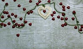 Vue la frontière de l'or et les coeurs rouges sur le fond en bois clair Images stock