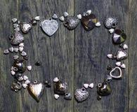 Vue la frontière des perles de coeurs sur le vieux fond en bois foncé Photos stock