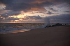 Vue large de vague se brisant sur la roche et se mélangeant avec les nuages photos stock