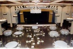 Vue large sur la pièce de boule de banquet dans le style de cru avec le sort des tables, des chaises et de la scène de théâtre image libre de droits