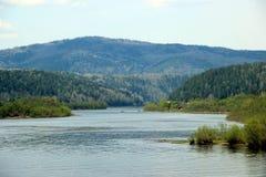 Vue le long de la rivière d'enroulement avec son bas-fond vers la montagne en bois Images stock