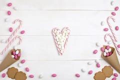 Vue les sucreries, les guimauves, les biscuits et les lucettes rayées sous forme de fond en bois blanc de vue supérieure de coeur photographie stock libre de droits