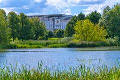 Vue luxueuse du bel étang avec une légère ondulation sur la surface avec l'élevage sur le rivage de l'herbe verte et Image libre de droits