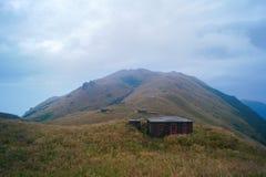 Vue maximale de prairie de coucher du soleil avec la maison en pierre abandonnée Photos libres de droits