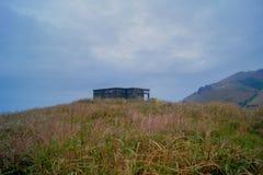 Vue maximale de prairie de coucher du soleil avec la maison en pierre abandonnée Photo stock