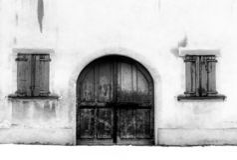 Vue monochrome d'un détail architectural d'un avant de maison avec des fenêtres et une grande porte en bois et de neige au sol images libres de droits