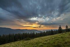 Vue panoramique d'été, vallée herbeuse verte sur le fond boisé éloigné de montagnes sous le ciel nuageux photos stock