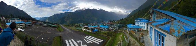Vue panoramique d'aéroport de Lukla avec des visiteurs du côté gauche et des maisons d'hôtes du côté droit Photos stock