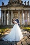 Vue panoramique d'un couple de nouveaux mariés de conte de fées étreignant et embrassant Image libre de droits