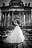 Vue panoramique d'un couple de nouveaux mariés de conte de fées étreignant et embrassant devant la vieille église ghotic baroque Photographie stock
