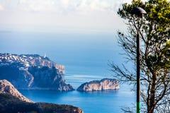 Vue panoramique de cap d'Ordonnateur national de La dans Javea, Espagne Un arbre et un réverbère dans le premier plan photo libre de droits