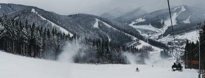 Vue panoramique de station de sports d'hiver de Bukovel de remonte-pente, de neige, de montagnes et d'arbres sur le fond photo libre de droits