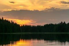 Vue panoramique sur le coucher du soleil lumineux au lac de forêt Image stock