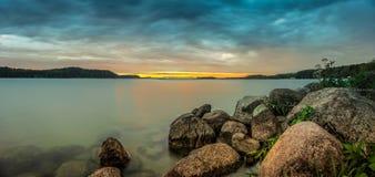 Vue panoramique sur le lac avec les nuages foncés sur le ciel et la roche sur le rivage photo stock