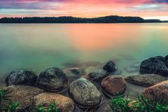 Vue panoramique sur le lac avec les nuages foncés sur le ciel et la roche sur le rivage image stock