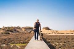 Vue par derrière d'un homme marchant avec son chien sur une route menant par le beau paysage Photos stock