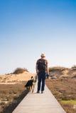 Vue par derrière d'un homme marchant avec son chien sur une route menant par le beau paysage Images libres de droits