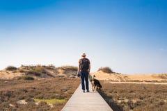 Vue par derrière d'un homme marchant avec son chien sur une route menant par le beau paysage Image stock
