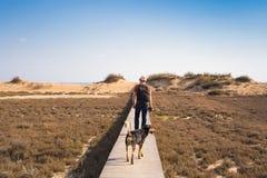 Vue par derrière d'un homme marchant avec son chien sur une route menant par le beau paysage Photographie stock libre de droits