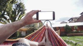Vue par derrière une jeune femme se situant dans un hamac et regardant le smartphone photo libre de droits