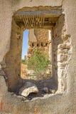 Vue par la fenêtre détruite des ruines du village abandonné Image stock