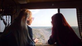 Vue par la fenêtre d'un autotrailer en mer entre deux femmes avec les cheveux débordants flottant dans le vent dans les rayons clips vidéos