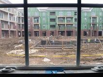 Vue par la fenêtre des hommes construisant la piscine Images libres de droits
