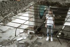 Vue par la grille Une fille seule dans un T-shirt blanc et des jeans se tient sur les ruines d'une maison ruinée Expression trist Photos libres de droits