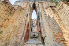 Vue par la porte à Wat Si Chum, un temple bouddhiste antique en parc historique de Sukhothai Images libres de droits