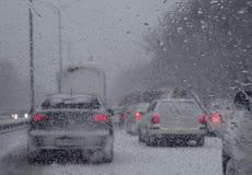 Vue par le pare-brise des véhicules bloqués sur la route aux chutes de neige images stock