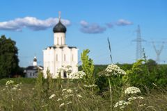 Vue par le pré de Bogolubovo vers l'église de l'intervention de la Vierge Marie sur la rivière de Nerl Image stock