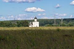 Vue par le pré de Bogolubovo vers l'église de l'intervention de la Vierge Marie sur la rivière de Nerl Images stock