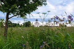 Vue par le pré de Bogolubovo vers l'église de l'intervention de la Vierge Marie sur la rivière de Nerl Photographie stock libre de droits