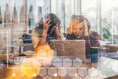 Vue par le verre Deux femmes d'affaires s'asseyent devant l'ordinateur portable, saisissant leurs têtes Séance de réflexion, trav Photographie stock libre de droits