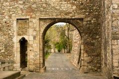 Vue par le vieil arc en pierre sur le trottoir Images stock