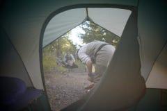 Vue par un aileron de tente des hommes dans un terrain de camping Photo libre de droits