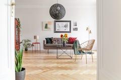 Vue par une porte ouverte dans un intérieur de salon avec les meubles éclectiques et un plancher en bois dur spacieux et uniques photos stock