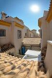 Vue parmi les maisons jaunes sur les tuiles de toit et les deuxièmes étages avec des tours l'espagne Image stock
