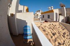 Vue parmi les maisons jaunes sur les tuiles de toit et les deuxièmes étages avec des tours l'espagne Photographie stock