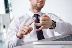 Vue partielle d'homme d'affaires comptant sur des doigts sur le lieu de travail Photos stock