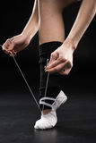 Vue partielle de danseuse de femme attachant la chaussure de ballet sur le noir Images stock