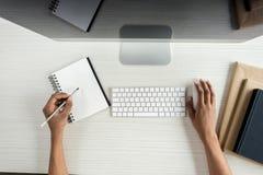 vue partielle de l'écriture d'étudiant dans le carnet et d'à l'aide des dispositifs numériques tandis que photographie stock libre de droits