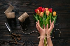 Vue partielle des mains, de la corde, des ciseaux et du bouquet femelles des fleurs photos libres de droits