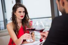 vue partielle des verres tintants de couples de vin rouge pendant la date romantique Photographie stock libre de droits