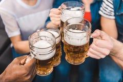 vue partielle en gros plan de jeunes amis tenant des verres de bière dans des mains Photos stock